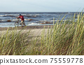 A man leads a bicycle on a sandy Baltic beach 75559778