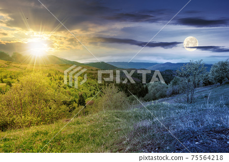 day and night equinox time change concept above mountainous countryside scenery in spring. trees and grass on hills rolling through green valley in to the distant ridge with sun and moon on the sky 75564218
