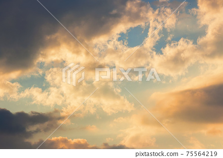 clouds in idyllic evening light. nature background in warm yellow and orange tones 75564219