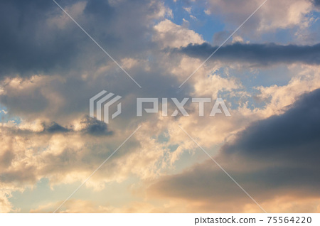 clouds in idyllic evening light. nature background in warm yellow and orange tones 75564220