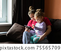 Mother and daughter at home use tablet pc. Motherhood, spending time with a child. Parental love. 75565709