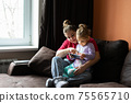 Mother and daughter at home use tablet pc. Motherhood, spending time with a child. Parental love. 75565710
