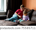 Mother and daughter at home use tablet pc. Motherhood, spending time with a child. Parental love. 75565711