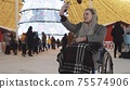 Young woman with dreadlocks in a wheelchair at Christmas party on the streets - taking selfie and smiling 75574906