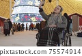 Young woman in a wheelchair at Christmas party on the streets - taking selfie and smiling 75574914