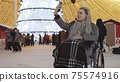 Young woman in a wheelchair at Christmas party on the streets - taking selfie 75574916