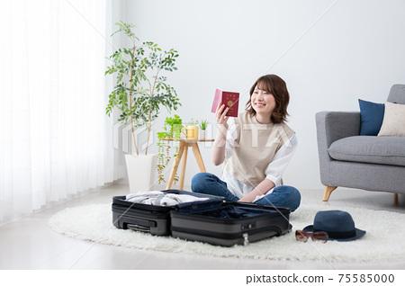 年輕女子為在客廳裡的海外旅行做準備 75585000