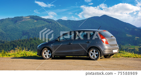 mizhhirya, ukraine - AUG 08, 2020: car on the concrete parking on top of the mountain in morning light. travel countryside concept. beautiful nature scenery views in summer with clouds on the blue sky 75588989