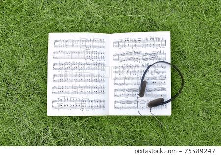 草坪上的耳機和樂譜 75589247