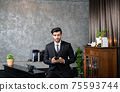 Business man in a suit using smartphone deal a customer and manage order. entrepreneur startup businessman using smartphone networking application checking email time business news. 75593744