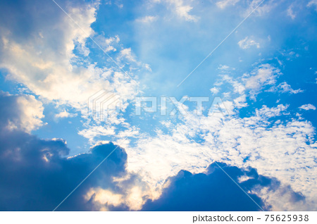 The sun ray behind the clouds in the blue sky. 75625938