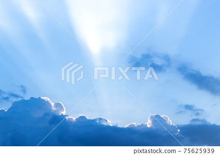 The sun ray behind the clouds in the blue sky. 75625939