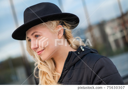 Portrait of a blonde woman wearing a Hearing Aid 75630307