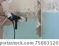 Worker removes old paint from a concrete wall 75663120