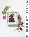 Easter composition with Pink tulips and chocolate bunny in gift box on white background 75664943