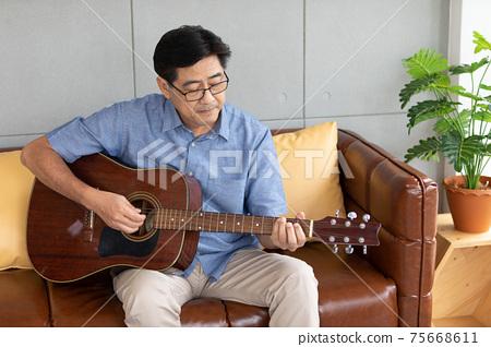 senior asian man playing guitar at home 75668611