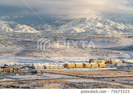 Aerial view of residential neighborhood against overcast sky and snowy mountain 75675525