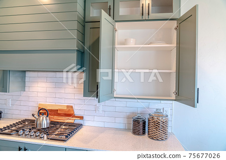 Built in cooking unit and wall cabinets inside the clean kitchen of a home 75677026