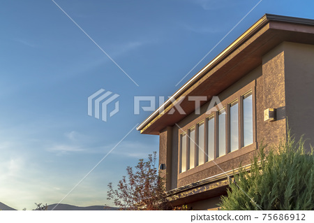 Sunlit house exterior with view of the upper storey against mountain and sky 75686912