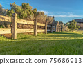 Brown wooden low fence on a lush green field against thick bushes and shrubs 75686913