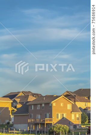 Beautiful landscape of houses and vast cloudy sky viewed on a bright sunny day 75686914