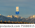 Drive Alert and Buckle Up road sign against snowy mountain and cloudy sky 75686915