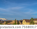 Beautiful landscape of houses with snow capped mountain and vibrant sky view 75686917