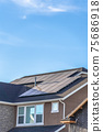 Gray roof of home with solar panels and pipe vents against blue sky background 75686918