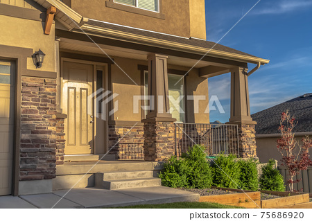 Home with stairs leading to the front door and porch against hill and sky view 75686920