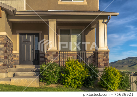 Stairs leading to porch and front door with sidelight at the entrance of home 75686921