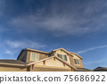 Home with front gable roof and dormers against vast blue sky with clouds 75686922