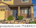 Home entrance with front porch gray door sidelight and garage with gable roof 75686923