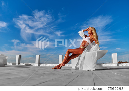 The young woman in white pareo on a terrace and blue sky on a background 75692984