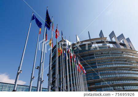 Strasbourg, France. August 2019.The entrance to the modern seat of the European parliament. A row of flagpoles with the flags of the member states of the European Union welcomes those who enter. 75695926
