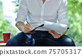 Businessman in casual wear sitting in park  with document 75705317