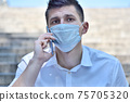 Young financial analyst in medical mask speaks on mobile phone. 75705320