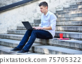 Businessman sitting on stairs and typing on laptop. 75705322