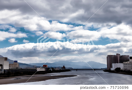 Bright white clouds are about to roll over the city of Kagoshima, in Japan. 75710896