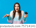 Surprised and wondered, amused cute caucasian woman in winter sweater, shrugging amazed, holding credit card and smartphone, got cashback, standing blue background joyful 75714141