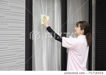 House cleaning woman cleaning windowpanes 75716059