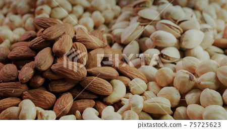 Bunches of assorted healthy nuts - almonds, pistachios, cashews and hazelnuts. Source of vitamins 75725623
