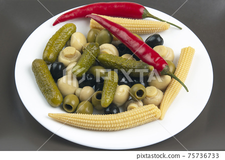 Olives, pickled cucumber, pepper, mushrooms and corn in a salad on a plate 75736733