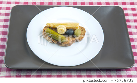 breakfast of canned and pickled olives, cucumber mushrooms with bread on a white plate 75736735