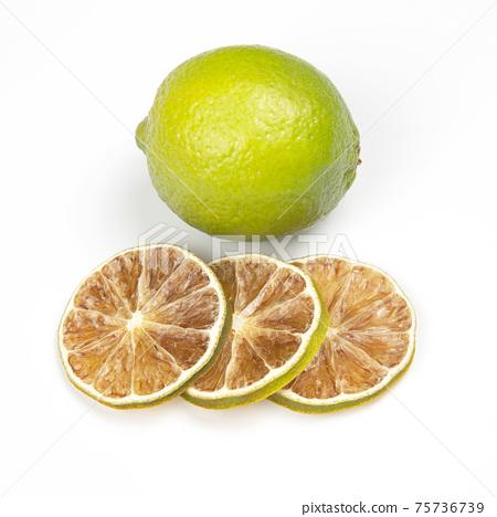 Dried green lemon slices next to fresh lemon on a white background 75736739