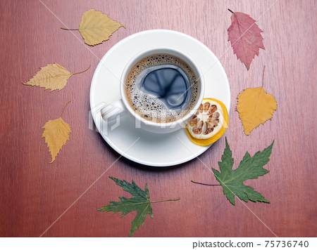 White cup with black coffee and autumn leaves 75736740