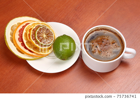 Dried slices of various citrus fruits and black coffee in a white Cup 75736741