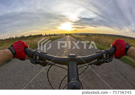 The cyclist rides on the road towards sunny sunset sky. Sports and travel. 75736745