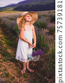 The little girl collects flowers on a lavender field 75739181