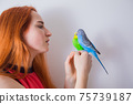 The beautiful woman admires her beautiful parrots 75739187