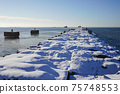 winter seascape, port entrance with snow covered concrete breakwater 75748553